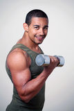 Tough gym guy. Tough smiling gym guy strength training with dumbbell Stock Images