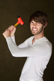 Tough Handy Man With Mallet. Young angry Caucasian man with mallet clenches his teeth Stock Images