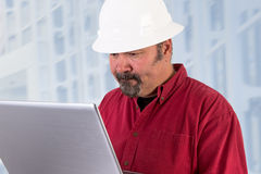 Tough Issues Arise. Hardhat worker working on the tough issues with his laptop, he has a serious thoughtful look that he values his job, he is wearing red shirt Stock Image