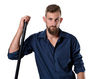 Tough looking young man with beard leaning on his hockey racket Royalty Free Stock Image