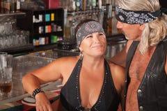 Tough Loving Couple in Bar. Mature biker gang female admiring men in bar Stock Photography