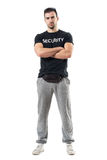 Tough macho bouncer wearing waist bag with crossed arms looking at camera. Full body length portrait isolated on white studio background stock photo