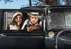 Tough Male and Female Gangsters. 1920s vintage gangsters in shoot out behind car door Royalty Free Stock Image