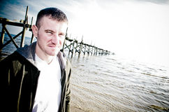 Tough Man. A man with an intense stare wearing a hooded sweatshirt with an old pier in the background Royalty Free Stock Photo