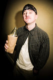 Tough Man Drinking Alcohol. A man drinking alcohol from a bottle in a paper bag Stock Photos