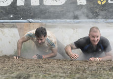 Tough Mudder 2015: Cry Baby. Boughton House, Northamptonshire, UK - May 31, 2015: A pair of Tough Mudders emerge from the eye-watering Cry Baby obstacle at the royalty free stock photography