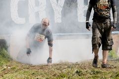 Tough Mudder 2015: Eye-watering Cry Baby. Boughton House, Northamptonshire, UK - May 30, 2015: A Tough Mudder emerges from the eye-watering Cry Baby obstacle at royalty free stock image