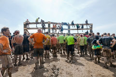 Tough Mudder: Facing the Next Challenge. Male and female racers climbing over an obstacle at the Tough Mudder competition in Mansfield Ohio on April 27, 2013 stock photo