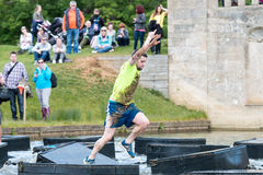 Tough Mudder 2015: Leaping. Boughton House, Northamptonshire, UK - May 30, 2015: A Tough Mudder leaps into action as he crosses the Island Hopper at the Tough royalty free stock image