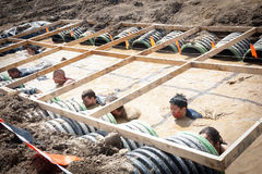 Tough Mudder: Racers in the Boa Constrictor Obstic. Male and female racers moving through the boa constrictor obstacle at the Tough Mudder competition in royalty free stock photo