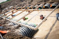 Tough Mudder: Racers in the Boa Constrictor Obstic. Male and female racers moving through the boa constrictor obstacle at the Tough Mudder competition in royalty free stock image