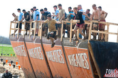 Tough Mudder: Racers Jumping off Walk the Plank. Male and female racers jumping off the Walk the Plank obstacle at the Tough Mudder competition in Mansfield Ohio stock photo