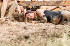 Tough Mudder 2015: Rolling in the mud. Boughton House, Northamptonshire, UK - May 31, 2015: A participant rolls through the Kiss of Mud obstacle at the Tough stock photography