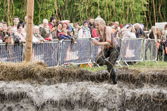Tough Mudder 2015: Shocking. Boughton House, Northamptonshire, UK - May 31, 2015: A lone Tough Mudder grimaces as she dashes through the shocking treatment of royalty free stock photography
