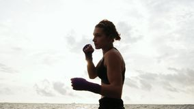 Tough pretty woman shadow boxing. Beautiful female boxer training by the sea on the beach in the morning, throwing. Punches in slowmotion stock footage