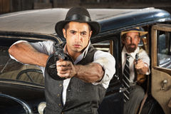 Tough 1920s Era Gangsters with Weapons. Tough 1920s vintage gangsters by car with weapons Royalty Free Stock Photos