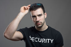 Tough security man taking off sunglasses with intense stare at camera Royalty Free Stock Photos