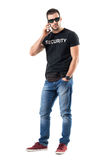Tough serious undercover policeman talking on the phone looking at camera. Full body length portrait isolated on white studio background Royalty Free Stock Photos
