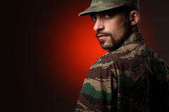 Tough soldier. Soldier looking at camera over shoulder royalty free stock photo