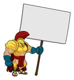 Tough Spartan or Trojan holding sign board. Cartoon illustration of a tough looking Spartan or Trojan soldier holding a sign board Royalty Free Stock Images