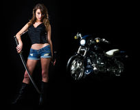 Tough woman. Attractive woman in shorts holding a samurai sword standing beside a harley motorcycle on black royalty free stock images