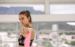 Woman exercising with resistance band at fitness studio. Tough woman using a resistance band in gym. Female exercising with resistance band at fitness studio Stock Photo