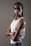 Tough young black man bicep and shoulder muscles. Shoulder and bicep muscles on tough young African American man with short dreadlocks, wearing grey vest with royalty free stock photos
