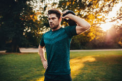 Tough young guy exercising with kettlebell in park Royalty Free Stock Images