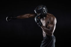 Tough young male boxer practicing. Side view of tough young male boxer practicing on black background. African athlete exercising boxing. Preparing for stock photo