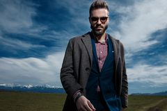 Tough young man holding his hand in his pocket. And confidently looking to the camera while wearing sunglasses, a gray coat and blue suit, standing on outdoor royalty free stock photo