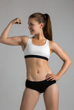 Tough young woman standing on grey background. Muscular female looking at camera.  bodybuilder wearing gloves ready for gym exerci. Tough young woman standing on Royalty Free Stock Photography