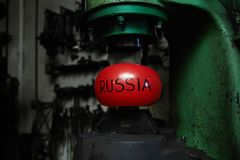 Toughness. Red inflated ball symbolizing Russia is situated between upper and lower parts of blacksmith machine royalty free stock photography