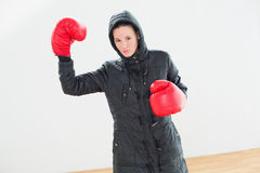Tought woman in hooded jacket and red boxing gloves Royalty Free Stock Image