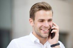 Toujours disponible La chemise blanche bien toilettée d'homme parlent le fond urbain de téléphone L'employé de bureau attirant be Image libre de droits