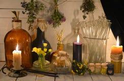 Toujours la vie alchimique ou pharmaceutique avec des pots, des herbes curatives et des bougies brûlantes Photographie stock libre de droits