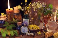 Toujours la vie naturelle avec la bougie, les bouteilles, les herbes curatives et les fleurs Photographie stock