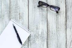 Toujours la vie noire et blanche : bloc-notes vide ouvert, carnets, stylo, verres Images stock
