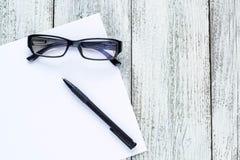 Toujours la vie noire et blanche : bloc-notes vide ouvert, carnets, stylo, verres Image stock