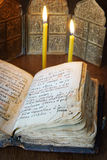 Toujours la vie religieuse avec le vieux livre ouvert et les bougies brûlantes Photo stock