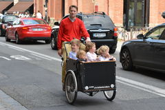TOULOUSE, FRANCE - JULY 23, 2016: Happy father and childrens riding velo biporter on the road in Toulouse, France. TOULOUSE, FRANCE - JULY 23, 2016: Father and Stock Image