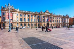 TOULOUSE, FRANCIA - 26 DE MARZO DE 2017: Turistas que caminan en Capitole de Toulouse, fachada del capitolio, ayuntamiento de Tou imagen de archivo