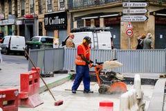 TOULOUSE, FRANKREICH - 10. AUGUST 2018 - Straßenarbeitskraft in der orange Uniform, die an Betondecke mit hydraulisch angetrieben lizenzfreies stockfoto