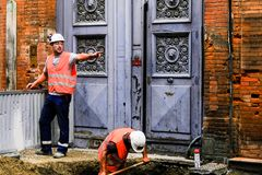 TOULOUSE, FRANKREICH - 10. AUGUST 2018 - zwei Straßenarbeiter auf der Straße Ein gibt Anweisungen und andere Grabungen eine Grube stockfotos