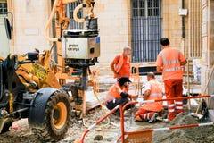 TOULOUSE, FRANKRIJK - AUGUSTUS 10, 2018 - Vier straatarbeiders in oranje uniformen bespreekt aanstaande bestratingsreparaties stock afbeelding