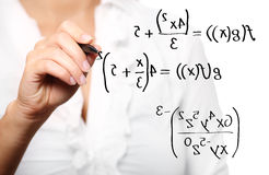Toung teacher solving a mathematical equation. A picture of a young teacher solving a mathematical equation over white background royalty free stock photo