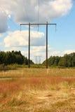 Tour électrique en bois dans le domaine d'herbe avec des nuages Images stock