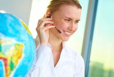 Tour agent. Portrait of smiling tour agent with headset consulting client online stock image