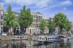 Tour boat in the Amsterdam canal belt. Royalty Free Stock Photos