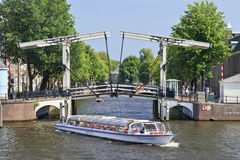 Tour boat in the Amsterdam canal belt. Stock Image