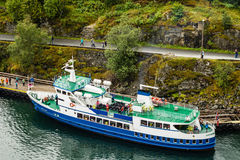 A tour boat anchored near the Norwegian fjord village of Flam in Norway. FLAM, NORWAY - CIRCA 2016: A tour boat anchored near the Norwegian fjord village of Flam Royalty Free Stock Images